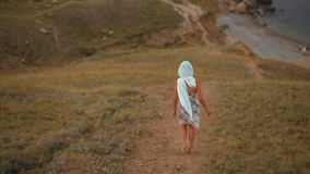 Slender Young Lady in a Headscarf and Dress Goes Down in the Mountains to Sea. Tanned Slender Young woman in a Headscarf and Dress Runs Down in the Mountains to stock video footage