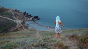 Slender Young Lady in a Headscarf and Dress Goes in the Mountains to the Sea stock video
