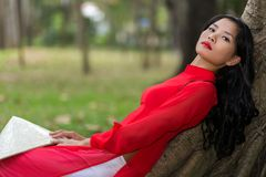 Slender young Vietnamese woman relaxing in a park Stock Photo