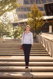 Slender young woman descending concrete stairs Stock Photos