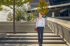 Slender young woman descending concrete stairs Stock Photography