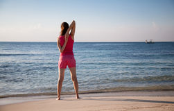 Slender young woman doing exercises on the sea coast Stock Image
