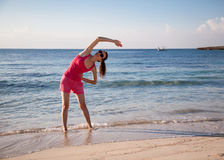 Slender young woman doing exercises on the sea coast Stock Photo