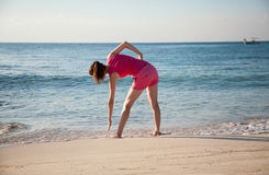 Slender young woman doing exercises on the sea coast Royalty Free Stock Photo