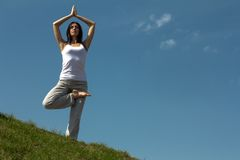 Slender young woman doing yoga exercise. Royalty Free Stock Images