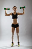 A slender young woman with a dumbbell on a gray background. Royalty Free Stock Image