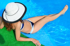 A slender young woman in a hat sits on the edge of the pool, sex Stock Photo