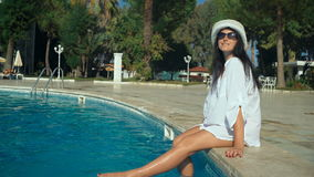 Slender young woman in a hat sits on the edge of the swimming pool, long legs.