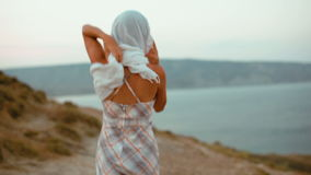 Slender Young woman in a Headscarf and Dress Goes in the Mountains to the Sea stock video