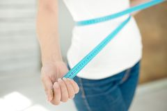 Slender young woman with a measuring tape royalty free stock images