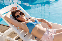 Slender young woman relaxing on chaise longue stock photography
