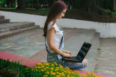 A slender young woman sitting with a laptop Stock Photos