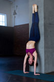 Slender young woman standing in inverted yoga pose performing handstand near the wall in sports studio Royalty Free Stock Photos