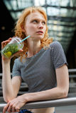 Slender young woman in striped shirt drinking refreshing mojito Stock Photos