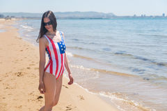 A slender young woman in a US flag walks along the coast Royalty Free Stock Photos