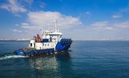 Slepend schip in de open zee, blauwe sleepboot die op overzees varen stock afbeeldingen