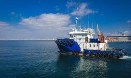 Slepend schip in de open zee, blauwe sleepboot die op overzees varen stock foto