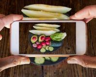 Slepenhanden die een mobiele telefoon houden die een fotografie van vegetab nemen stock foto