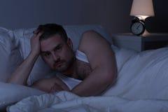 Slepless man som är vaken i säng Royaltyfria Foton
