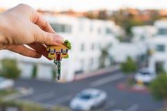 Sleutel in de vorm van een huis in de hand Stock Foto's