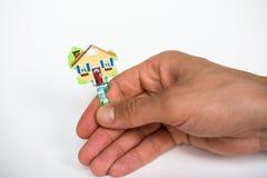 Sleutel in de vorm van een huis in de hand op witte achtergrond Stock Fotografie