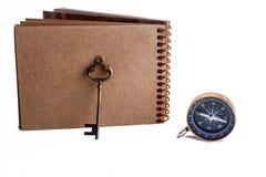 Sleutel, kompas en spiraalvormig notitieboekje Stock Afbeelding