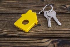 Sleutel met geel gevormd huis keychain op ketting op houten textuurachtergrond stock afbeeldingen