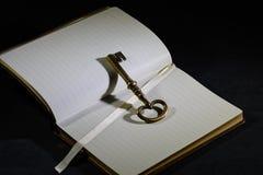 Sleutel op dagboek of notitieboekje stock afbeelding
