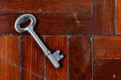 Sleutel op houten vloer Stock Afbeeldingen