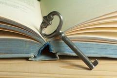 Sleutel tot kennisconcept Boek met sleutel op houten achtergrond Stock Fotografie