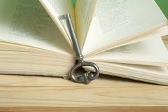 Sleutel tot kennisconcept Boek met sleutel op houten achtergrond Royalty-vrije Stock Afbeeldingen