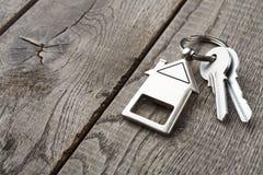 Sleutelbos met huis keychain op rustiek hout wordt gevormd dat stock fotografie