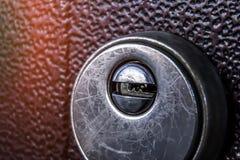 Sleutelgatclose-up op bruine deurachtergrond stock afbeelding