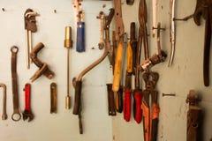Sleutels in de garagehulpmiddelen Oude hulpmiddelen die op muur in workshop, Hulpmiddelplank tegen een muur in de garage hangen stock foto's