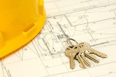 Sleutels en hoed over een bouwplan stock afbeeldingen