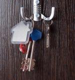 Sleutels en Huis keychain op houten achtergrond gestalte die worden gegeven die Stock Foto