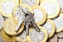 Sleutels op een achtergrond van muntstukken Stock Afbeeldingen