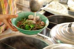 Sleven tömms i en bunke av nudlar som lagar mat nudeln i thai royaltyfria bilder
