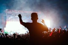 Slhouette молодого человека на концерте стоковое изображение rf