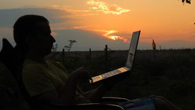 Slhouette of happy business man with laptop working on the field at sunset time. Man swinging on chair stock video footage