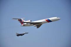 Sliac Slovakien - Augusti 27, 2011: Flygskärm av stråltrafikflygplantupoleven Tu-154M som eskorteras av strålluftfigh Arkivfoton