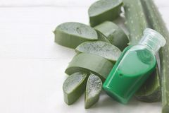 Slice Aloe Vera and green bottle gel placed on a white wooden royalty free stock image