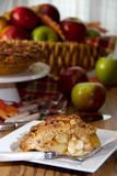 Slice of apple pie with basket of apples. Slice of deicious apple pie on plate -- propped with basket of apples in background, apples forks, server, and cake stock images
