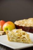 Slice of apple pie with copy space. Slice of freshly made apple pie with pastry lattice top, on flat plate with apples, cinnamon sticks and the rest of the pie stock photography