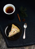 Slice of apple pie, cup of tea and tea spoon on dark table Royalty Free Stock Photography