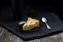Slice of apple pie, cup of tea and tea spoon on dark table Royalty Free Stock Photo