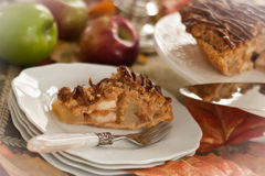 Slice of apple pie fork on plate. Slice of deicious apple pie on plate -- propped with basket of apples in background, apples forks, server, leaves and cake royalty free stock image