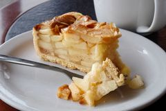 A slice of apple pie with pie on fork on white ceramic plate nex. T to a fork. Black and brown table Stock Photo