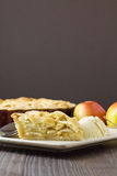 Slice of apple pie and ice cream, vertical. Slice of freshly made apple pie, a la mode, with pastry lattice top on flat plate with apples, cinnamon sticks and stock image