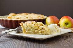 Slice of apple pie and ice cream, wide and horizontal. Slice of freshly made apple pie, a la mode, with pastry lattice top on flat plate with apples, cinnamon royalty free stock photos